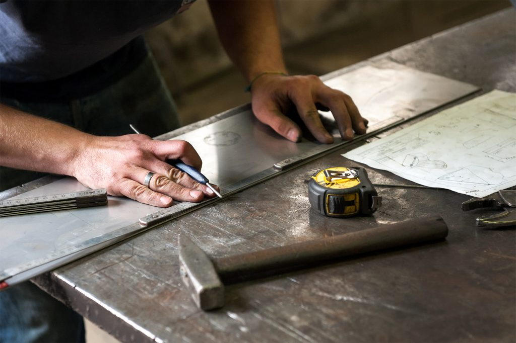 How best residential elevator is made - Metalworker marking measurements on a piece of sheet metal using a ruler and tape measure using dimensions from a plan on a sheet of paper on the workbench